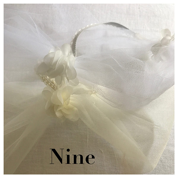 Le headband Nine de la collection mariage Epouse-Moi est un modèle rétro. Il se compose de tulle blanc ou ivoire, avec des fleurs en soie de chaque côté.