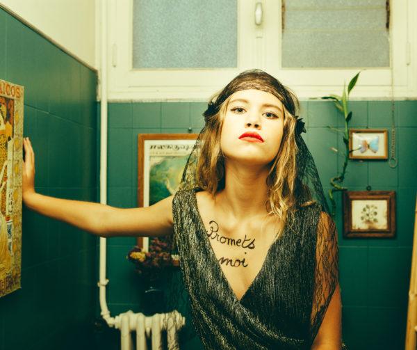 Le headband Ida de la collection Courtise-Moise compose de dentelle noire avec des fleurs en soie de chaque côté.