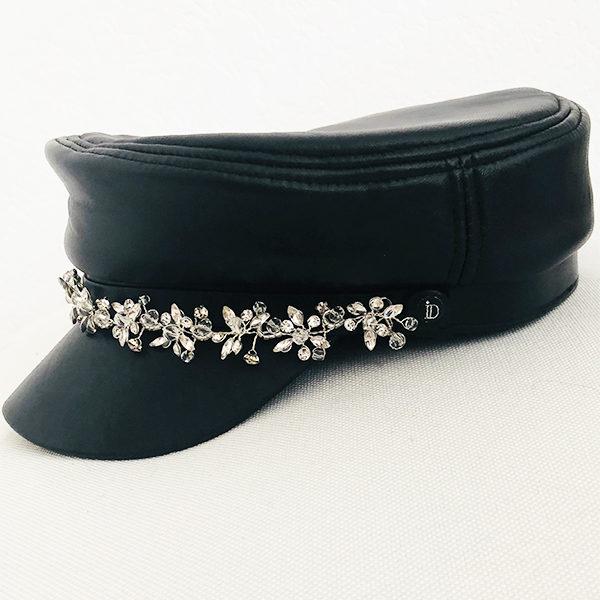 La Casquette des Saintes Ida Degliame est un modèle en cuir noir avec un bijou en strass