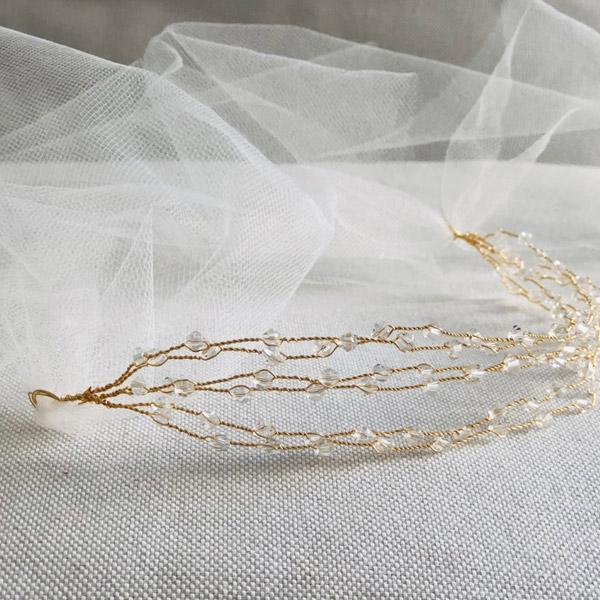 Des cristaux viennent se poser avec parcimonie sur la structure dorée du headband VENUS IDA DEGLIAME collection mariage