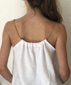 Le top LUCE IDA DEGLIAME couleur blanc, se règle grâce à son lien de cuir coulissant.